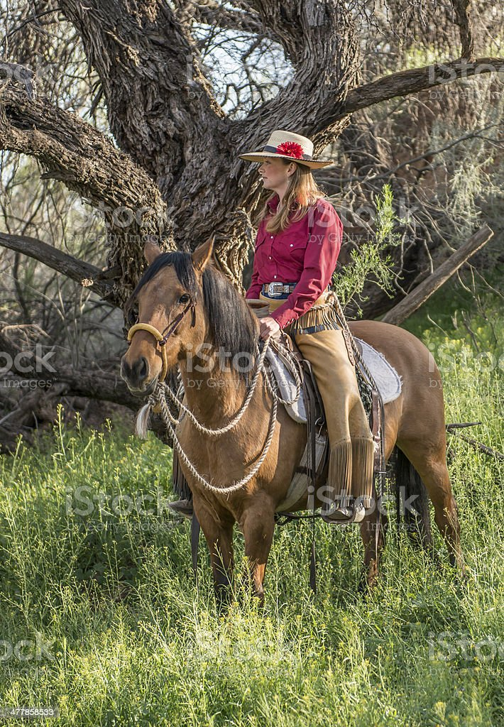 Cowgirl waiting on horse royalty-free stock photo