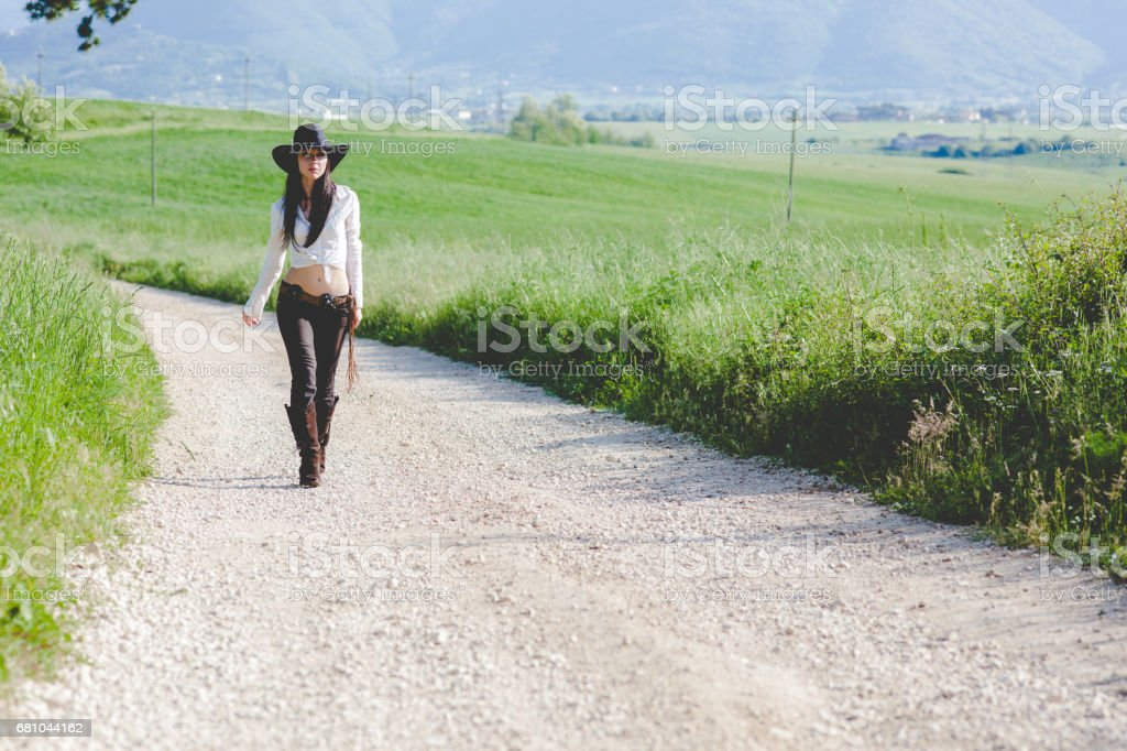 cowgirl walking on italian countryside royalty-free stock photo