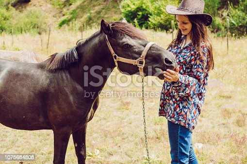 Young cowgirl with a colt on the ranch