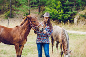 Young cowgirl with colts on the ranch