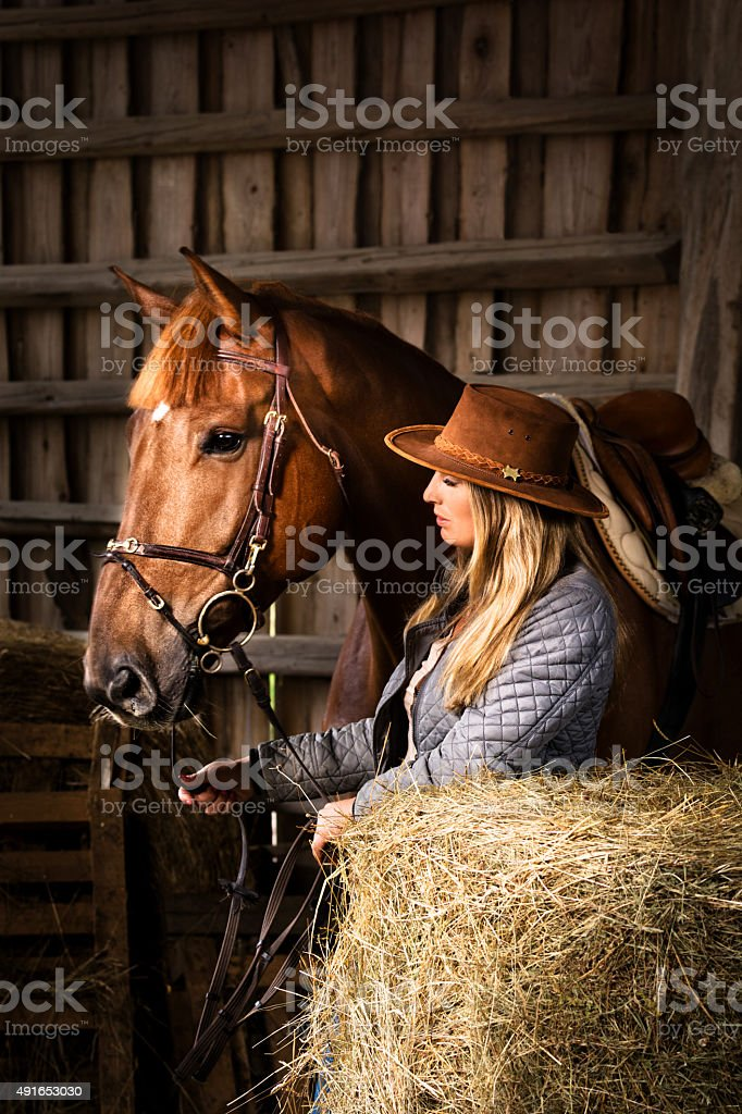 Cowgirl with her horse in barn next to hay bales stock photo