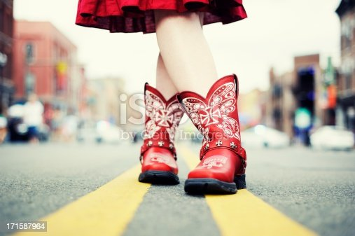A cowgirl in red cowboy boots and dress has her legs crossed, standing on the double yellow line in the middle of a city street. Ground level view of the boots and legs. Taken in Nashville, Tennessee, USA.