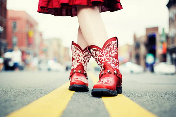 Cowgirl with Red Boots in the Road stock photo