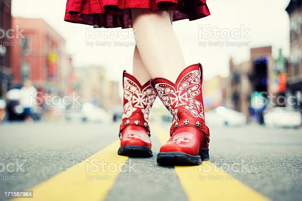 Cowgirl With Red Boots In The Road Stock Photo - Download Image Now