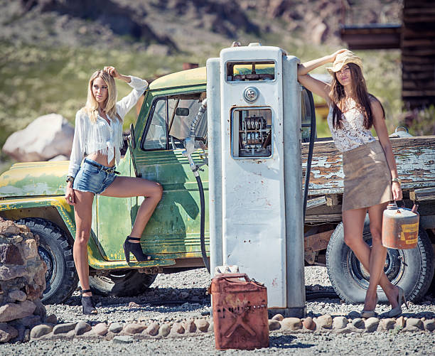 Cowgirls at the Oldtimer Gasstation Beautiful fashion models posing beside an Oldtimer Gasstation in the middle of the desert. sexy girl in blue jeans stock pictures, royalty-free photos & images