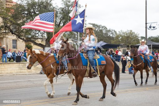 Bandera TX, USA- November 9, 2013- Cowgirls riding horses, carrying American and Texas flags in Veterans Day Parade.