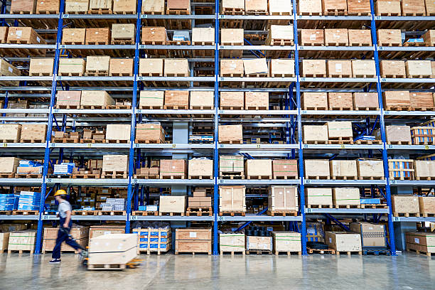 Coworker carrying cardboard box in warehouse. Cardboard boxes on shelves in warehouse. Storhouse. warehouse interior stock pictures, royalty-free photos & images