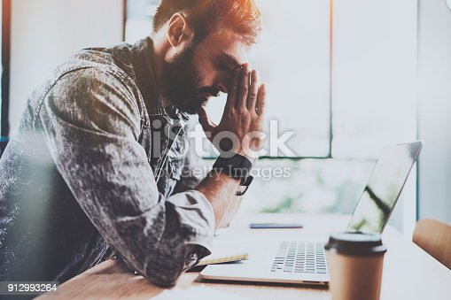 912969272istockphoto Coworker working process at sunny office.Tired young bearded man making pause after hard work day.Horizontal.Blurred background. 912993264