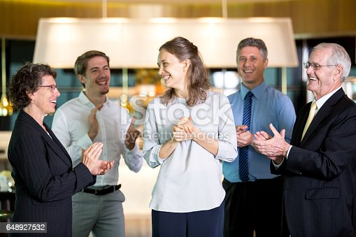 878220300 istock photo Coworkers Applauding to Happy Young Female Manager 648927532
