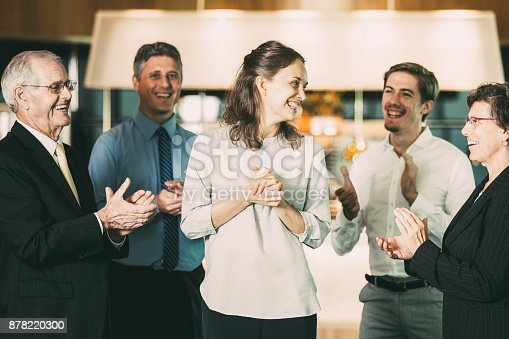 istock Coworkers Applauding to Happy Young Female Manager 878220300