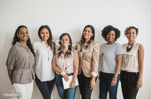 Group of women at office, posing for business portrait. Looking at camera.