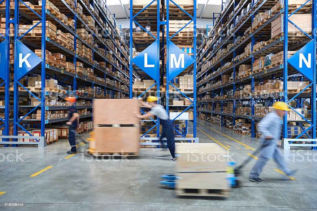 Coworkers carrying cardboard box in warehouse. stock photo