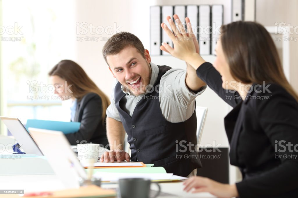 Coworkers celebrating achievement at office royalty-free stock photo