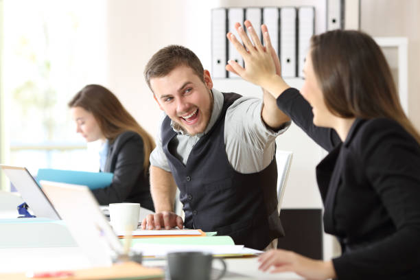 Coworkers celebrating achievement at office stock photo