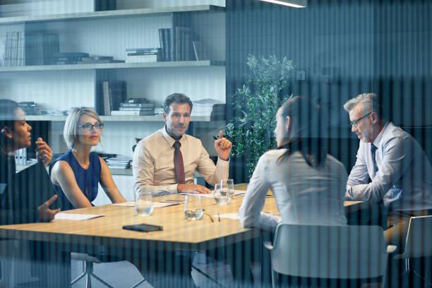 mitarbeiter kommunikation am schalter durch glas gesehen - großunternehmen stock-fotos und bilder