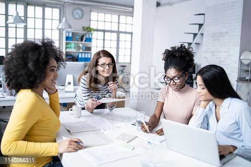 istock Coworkers discussing ideas and using laptop at work 1140066311