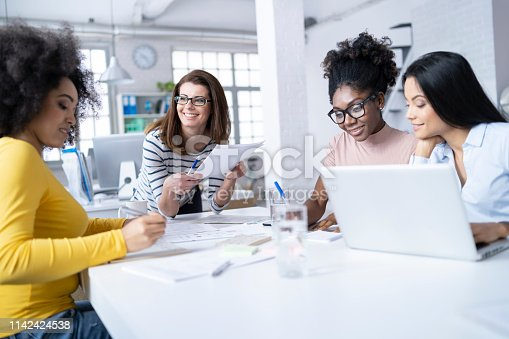 istock Coworkers discussing ideas and using laptop at work 1142424538