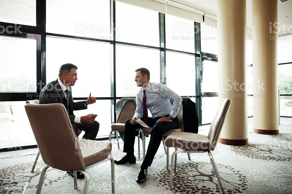 Coworkers discussing project in conference room stock photo
