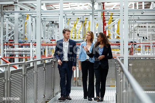 Confident multi-ethnic coworkers discussing in automobile industry during meeting. Full length of colleagues are walking on walkway in factory. They are wearing businesswear.