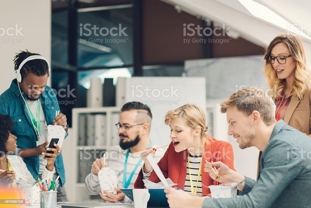 Young creative startup business team eating chines fast food. They...