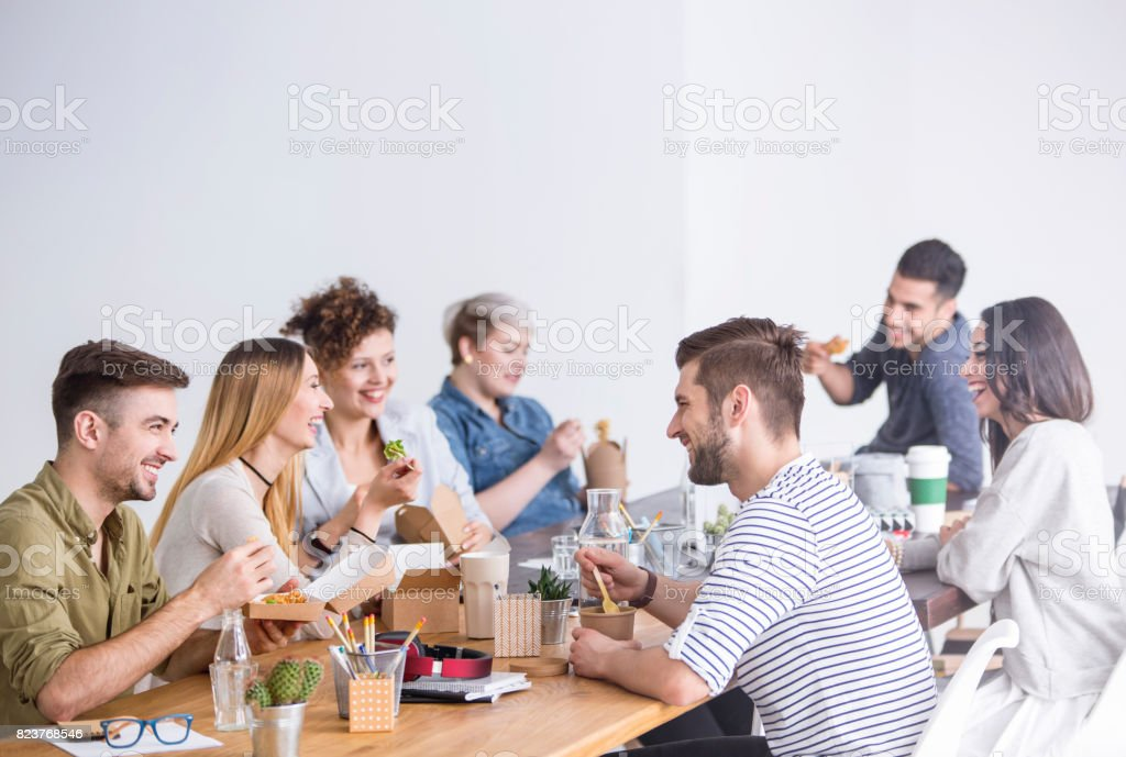 Coworkers eating lunch together stock photo