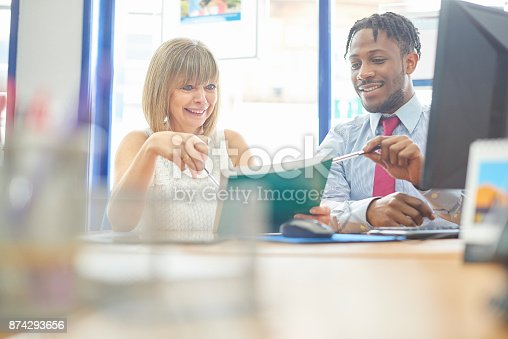 istock Coworkers going through files 874293656