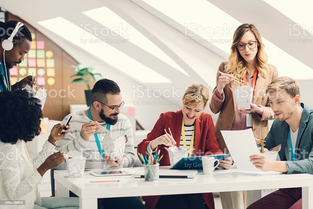 Coworkers Have Lunch Break in their startup Office. stock photo