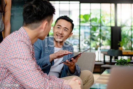 Coworkers having an informal meeting in a modern office. Hong Kong 2019