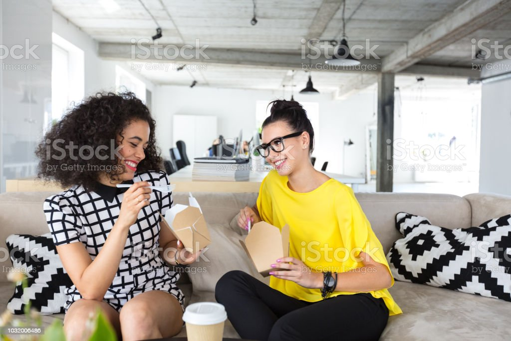 Coworkers having lunch break in office Two businesswomen having lunch break in office. Female colleagues sitting on couch and eating some food. 20-24 Years Stock Photo
