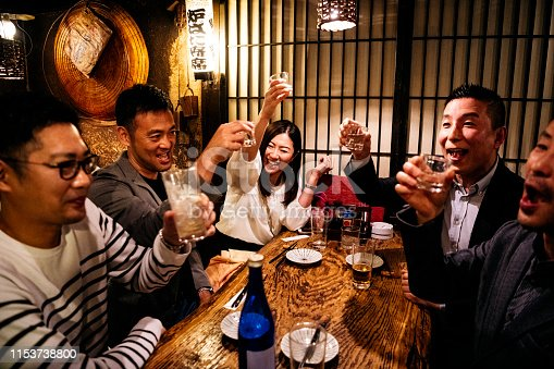 Group of friends drinking after work together in Izakaya, celebrations, teamwork, bonding