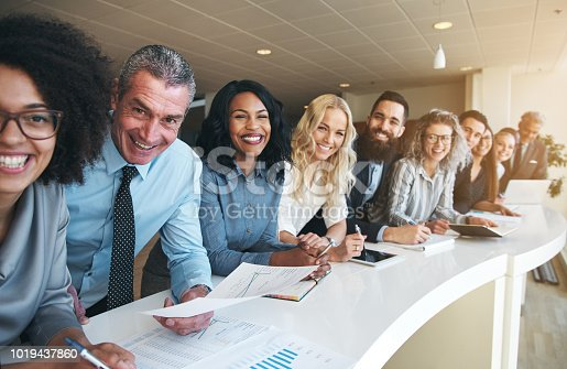 istock Coworkers in office smiling and looking at camera 1019437860