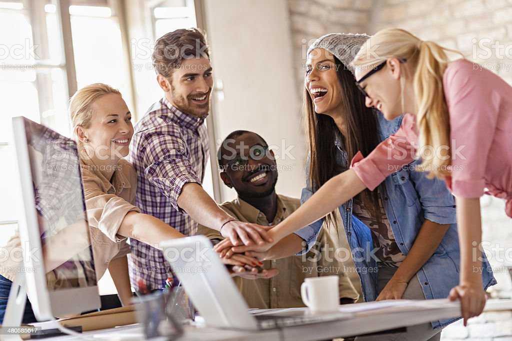 Coworkers joining hands stock photo