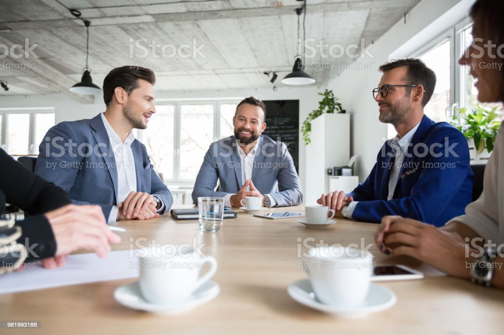 Coworkers making great meeting discussion Team of coworkers making great meeting discussion in modern co working office. Businessman talking colleagues in meeting. Adult Stock Photo