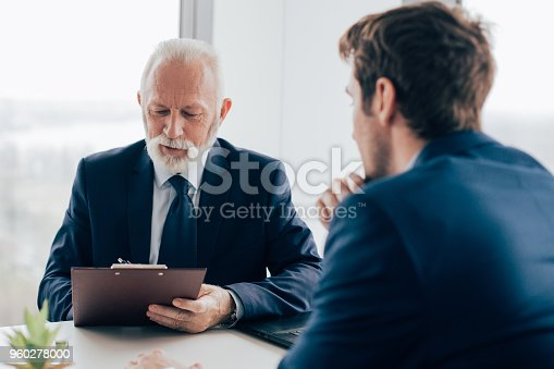Handsome senior man and younger version of himself sharing an office