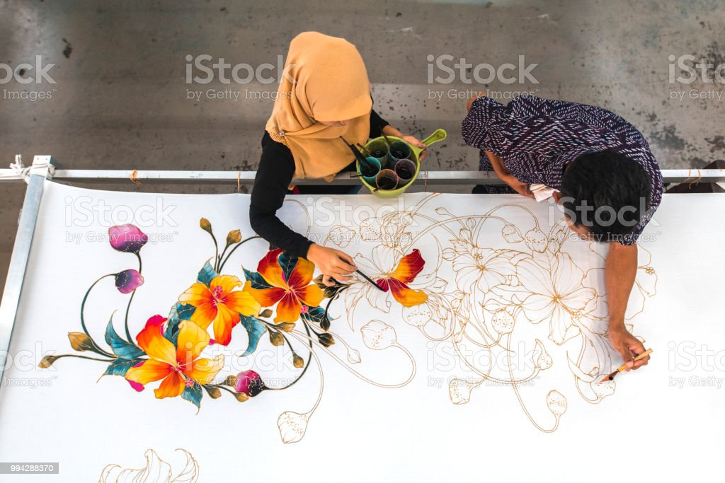 Coworkers painting in a batik workshop stock photo