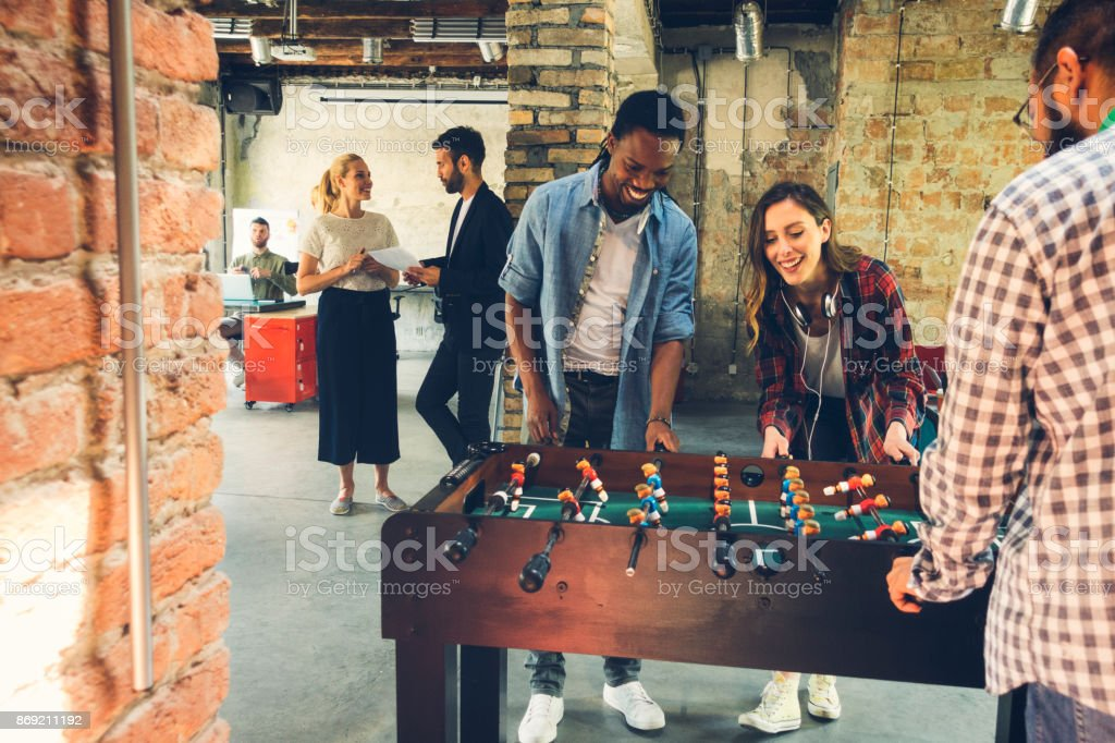 Coworkers playing foosball stock photo