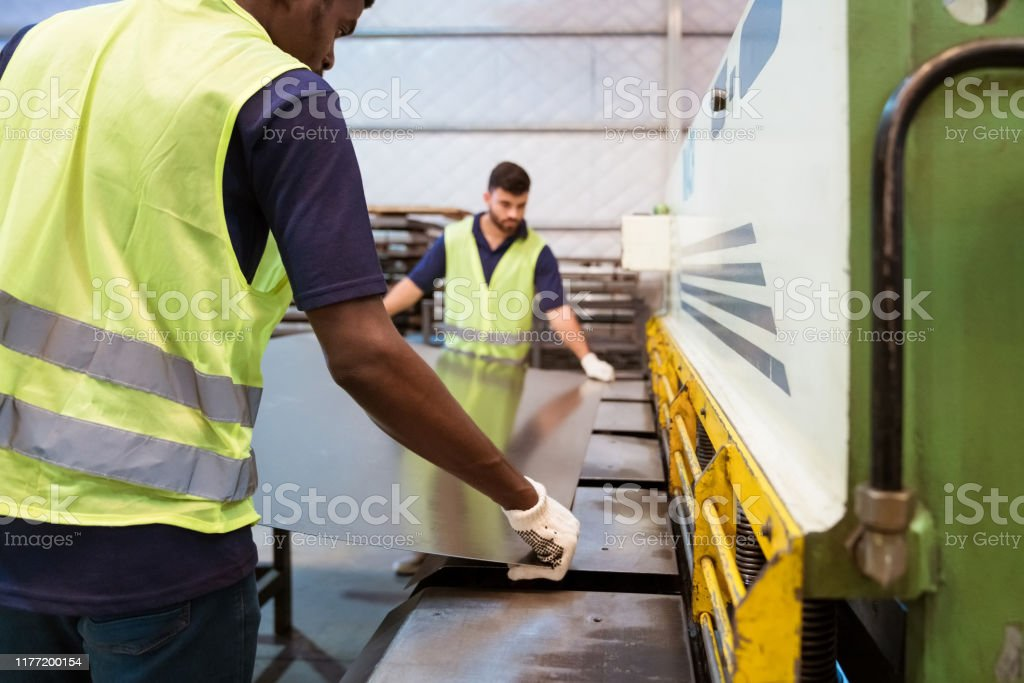 Coworkers putting sheet in guillotine machine Male colleagues adjusting metallic sheet on guillotine machine. Young trainees are in protective workwear. They are in industry. 20-24 Years Stock Photo