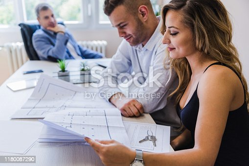 938640610 istock photo Coworkers revising blueprints 1180087290