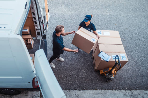 Coworkers rushing to load packages in a delivery van Delivery workers using a Hydraulic Hand Pallet Truck to load a delivery van. delivery man stock pictures, royalty-free photos & images