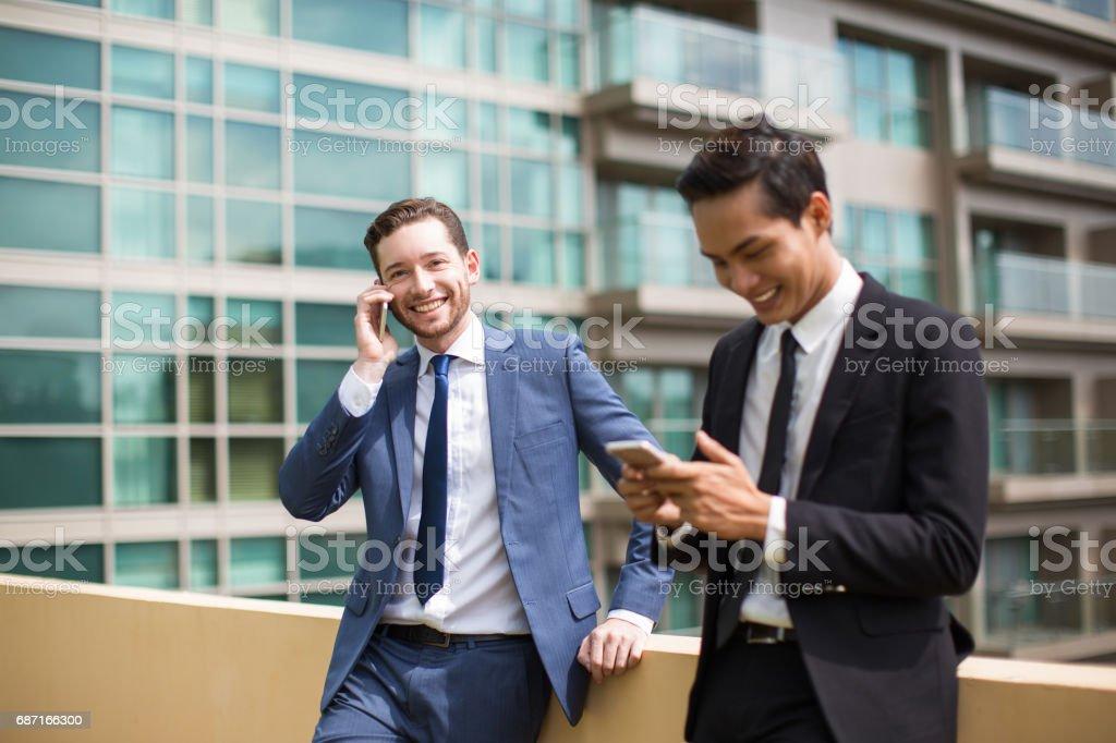 Mitarbeiter sprechen und SMS auf Handys außerhalb Lizenzfreies stock-foto