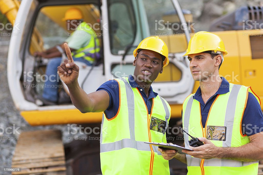 co-workers talking at construction site stock photo