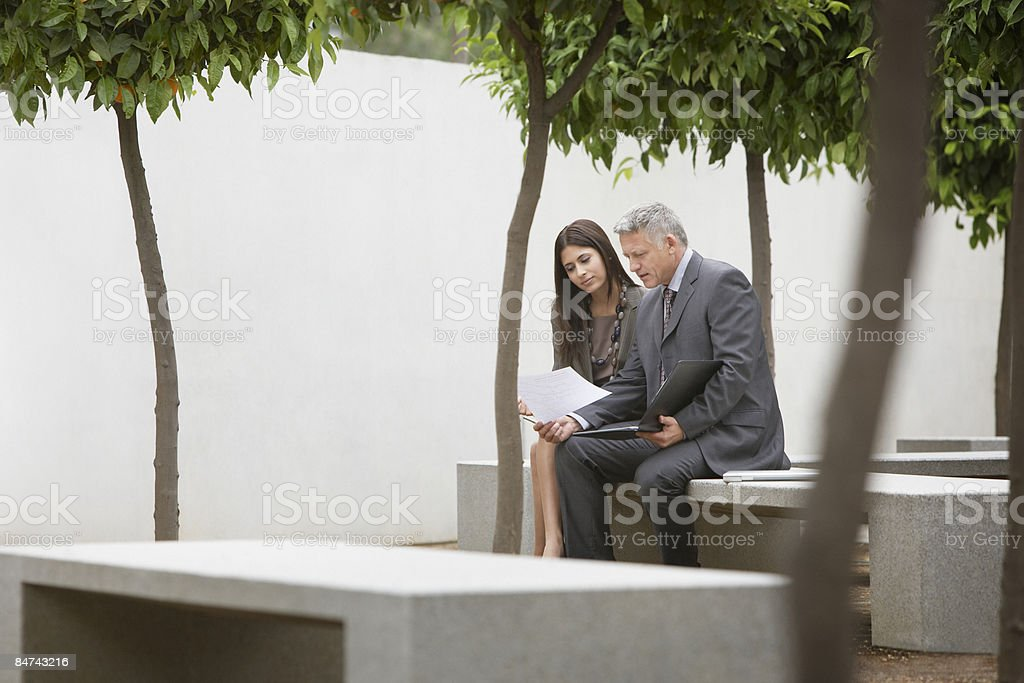 Co-workers talking in office building courtyard royalty-free stock photo