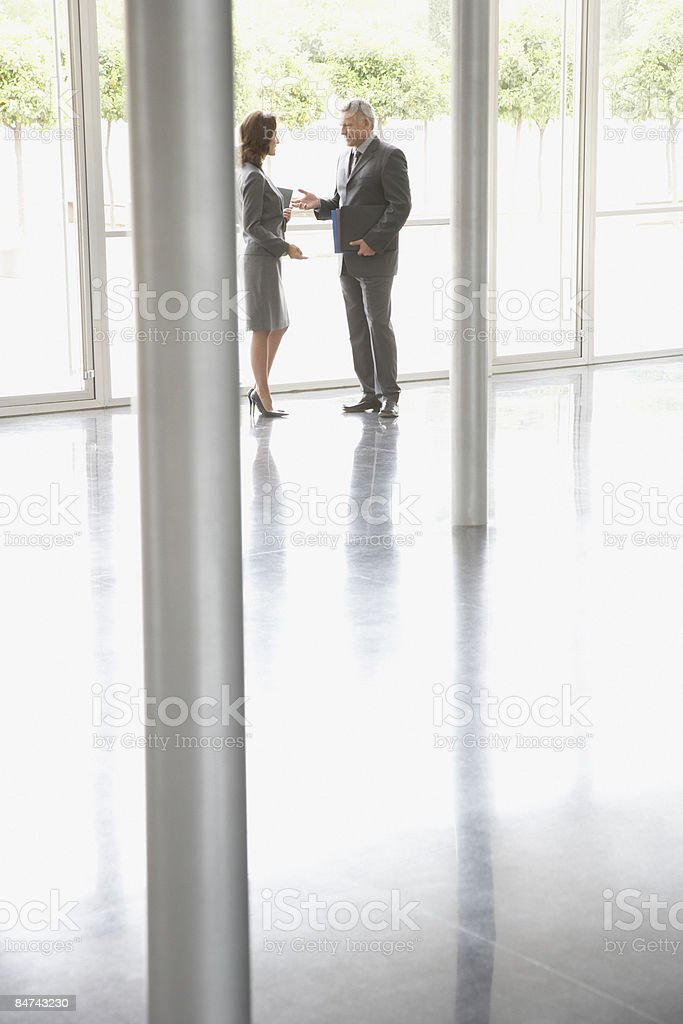 Co-workers talking in office lobby royalty-free stock photo