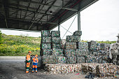 Male and female waste management workers in protective suits and hardhats standing outdoors next to stacks of compacted and bundled recyclables.