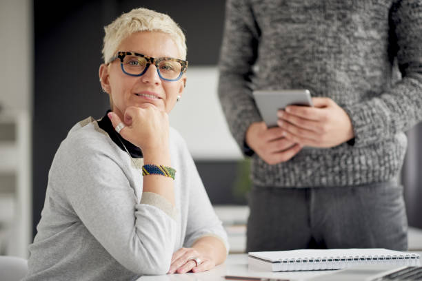 coworkers using tablet device - senior business woman tablet imagens e fotografias de stock