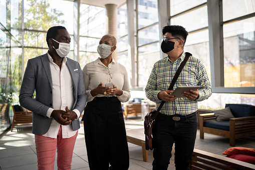 Coworkers walking and talking at office's lobby - with face mask