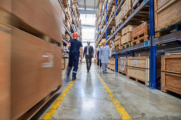 Coworkers walking box in warehouse aisle. stock photo