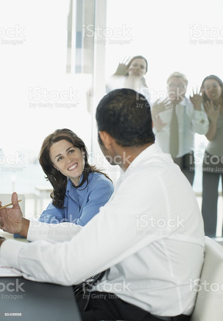 Co-workers watching businesspeople having meeting in conference room stock photo