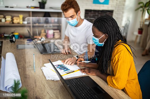 African woman and redhead man sitting at desk and working together on graphs while their colleagues relaxing behind them. They are wearing protective face masks during coronavirus pandemic