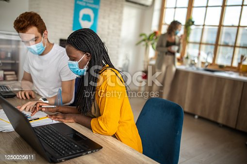 1124783373 istock photo Coworkers with protective face masks looking at graph and talking about business strategy at office 1250025611